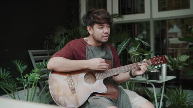 ung man musiker med videosamtal på smartphone spelar gitarr hemma - gitarrist bildbanksvideor och videomaterial från bakom kulisserna