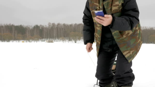 young man on a frozen lake with a phone looking for the desired route. he pulls on his sleigh things - solo bambini maschi video stock e b–roll