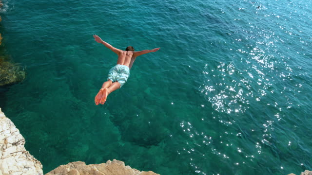 copy space:在陽光明媚的日子里,暑假的年輕人會跳懸崖。 - 懸崖 個影片檔及 b 捲影像