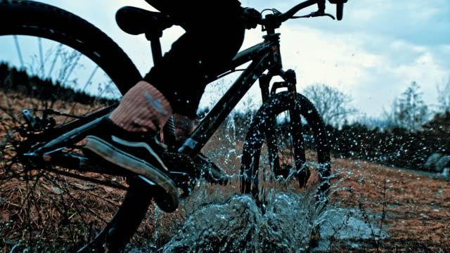ms young man su bicicletta bmx che spruzza in acqua - andare in mountain bike video stock e b–roll