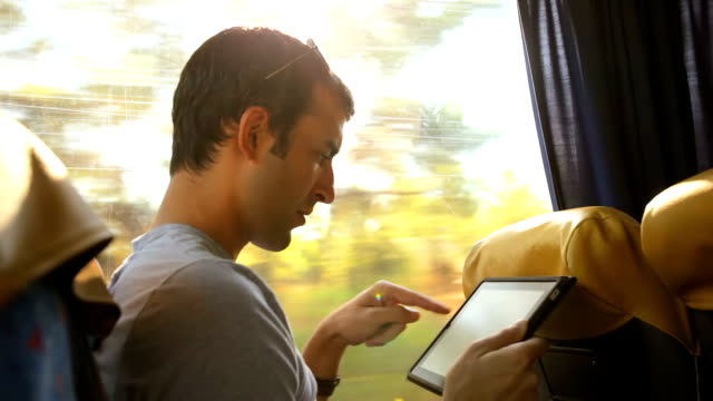 Young man on bus with tablet computer video