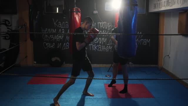 vídeos de stock, filmes e b-roll de jovem em treinamento de kick box com seu treinador - artes marciais