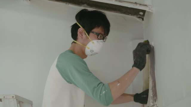 diy ung man på stege rengöring och reparationer i köket. - kvinna ventilationssystem bildbanksvideor och videomaterial från bakom kulisserna