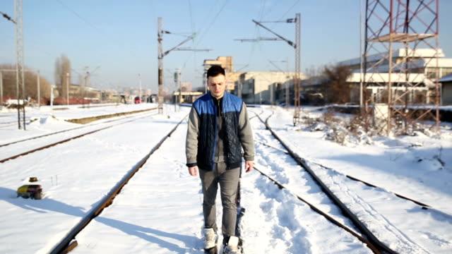 Young man on railway tracks