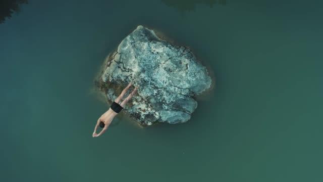 airon 關閉上臺下: 年輕人在暑假跳頭第一進入清澈的綠色湖水茶點在炎熱的晴天.海邊或森林的暑假。 - 懸崖 個影片檔及 b 捲影像