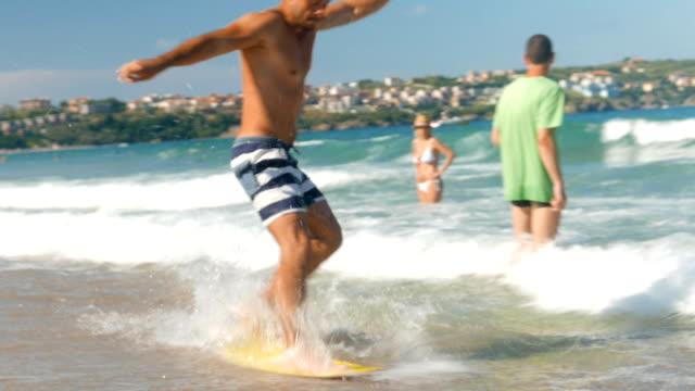 ung man på stranden försöker surfa en wake board men misslyckas och faller i vattnet - ofullkomlighet bildbanksvideor och videomaterial från bakom kulisserna