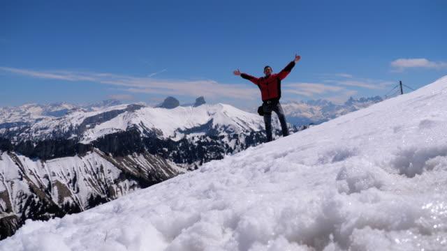 stockvideo's en b-roll-footage met jonge man op de top van de alpen bergen springt en verheugt het doel. zwitserland - sober leven