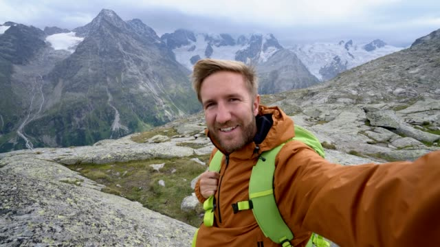Young man on top of a mountain takes a selfie portrait with glacier view video