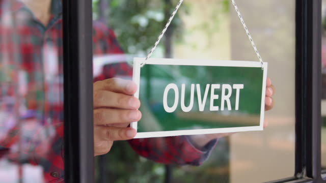 slow-mo: young man opening a french shop - open sign stock videos & royalty-free footage