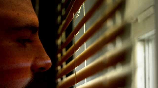 young man opening blinds in home - penombra video stock e b–roll