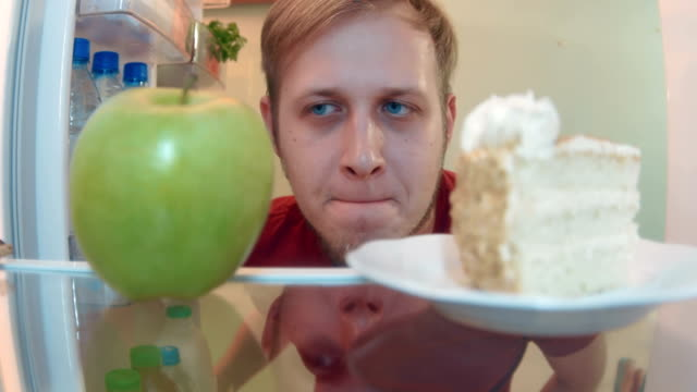 Young man opens the fridge choosing between an apple and cake and chooses cake video