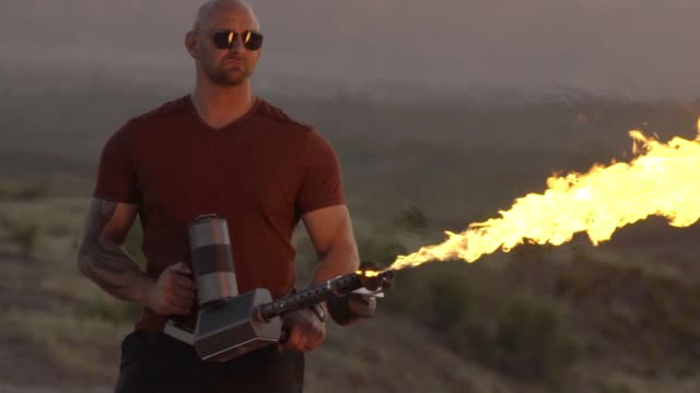 young man operating a flame thrower in the desert - autorità video stock e b–roll