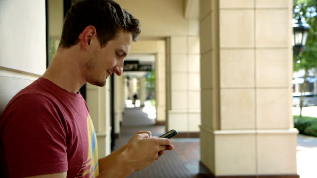 young man outdoor texting on his smart phone video