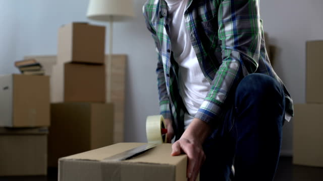 ung man packboxar med grejer, flyttar från lägenhet, hyra kontrakt - omlokalisering bildbanksvideor och videomaterial från bakom kulisserna