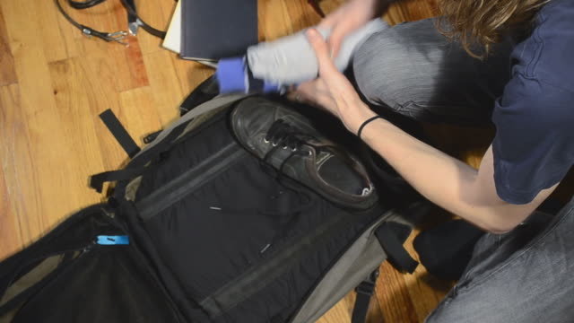 young man packing suitcase video