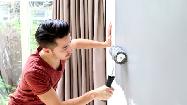 Young man painting wall with paint roller video