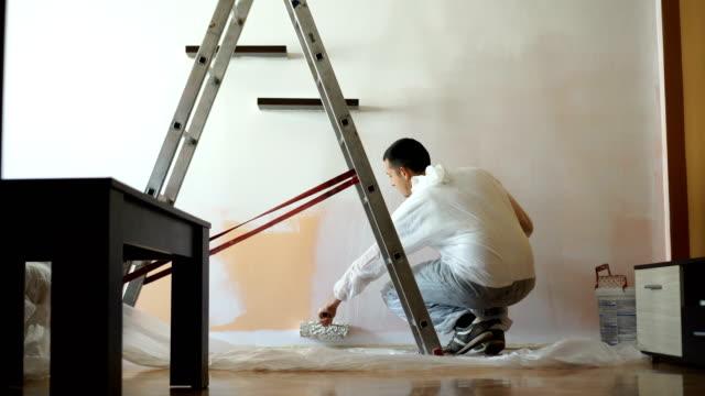 vídeos de stock e filmes b-roll de young man paints the wall - white wall
