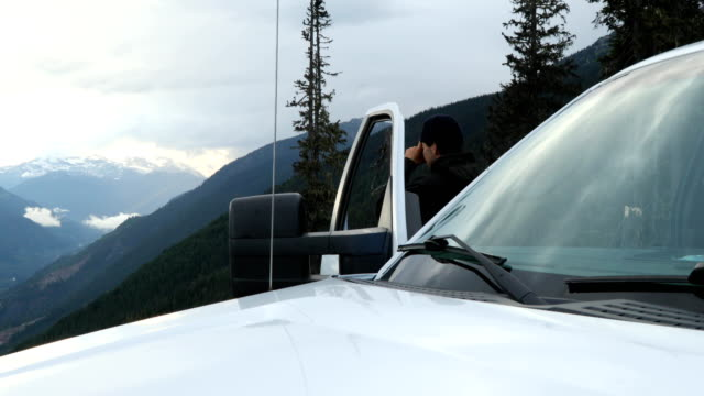 Young man pauses next to his vehicle to take photo of wild mountain scene