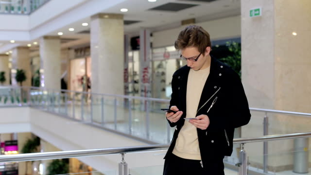 vídeos de stock e filmes b-roll de young man pays for purchases by credit card using the phone in a mall. - online shopping