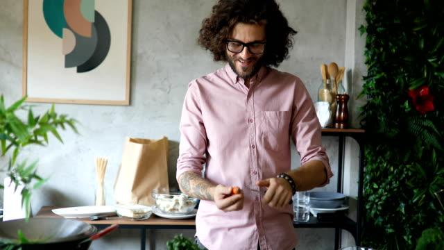 junger mann schälen karotten in der heimischen küche - geschält stock-videos und b-roll-filmmaterial