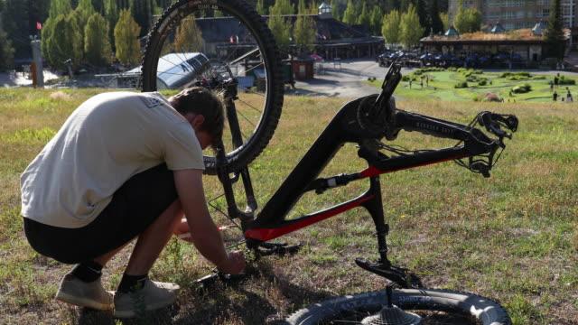 vidéos et rushes de le jeune homme effectue des réparations de vélo de montagne près du parc de vélo - évasion du réel