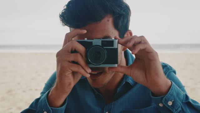 Young man photographing through camera at beach