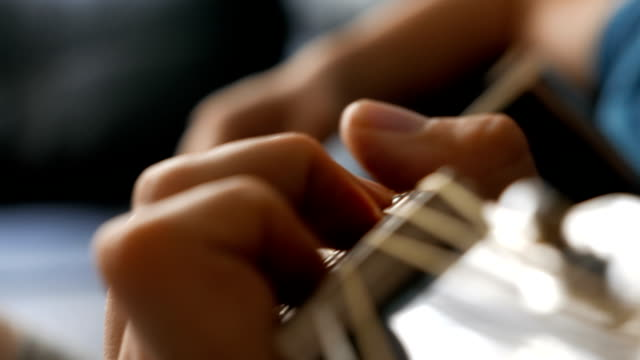 Young man playing a black acoustic guitar video