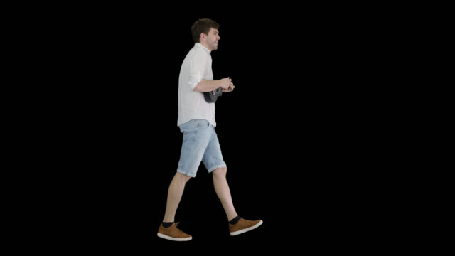 Young man playing a ukulele, singing and walking, Alpha Channel