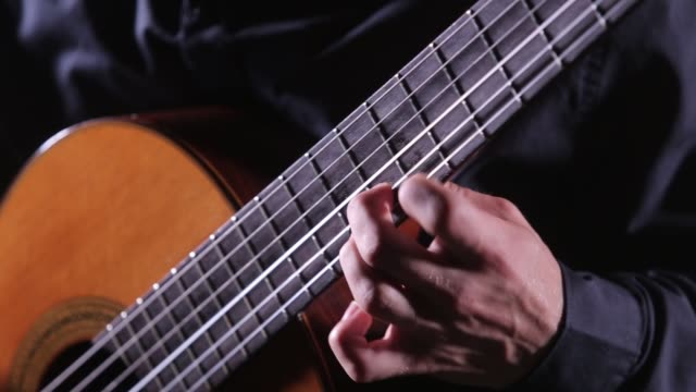 young man playing an acoustic guitar - tradycja filmów i materiałów b-roll