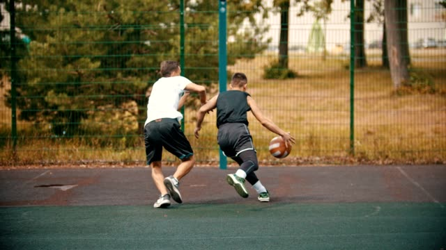 young man playing basketball on the sports ground with friend - dribbling, avoiding his opponent and throwing a ball - miss - cestino video stock e b–roll