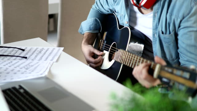 Video Young man playing guitar at home