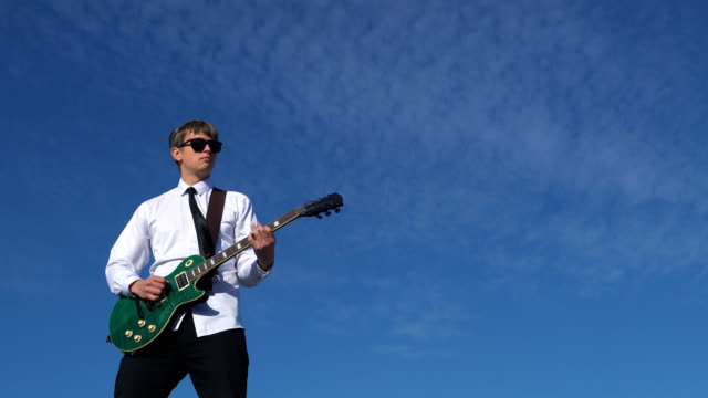 Young man playing guitar on against a blue sky. 4k