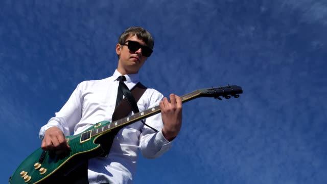 vídeos de stock, filmes e b-roll de homem novo que joga a guitarra sobre de encontro a um céu azul. 4k - artista