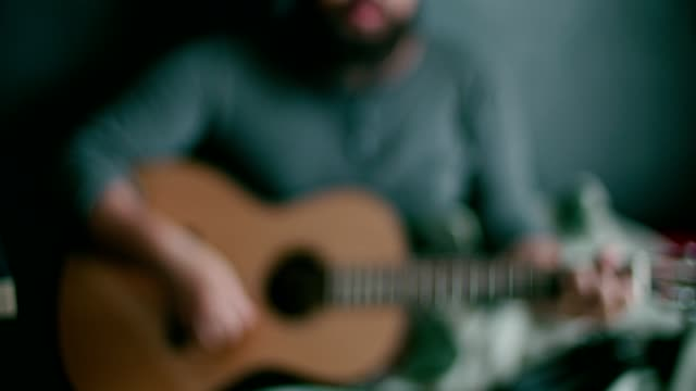 vídeos de stock, filmes e b-roll de homem novo que joga o guiter em casa - música acústica