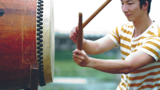 Young man playing Japanese drum outdoors video