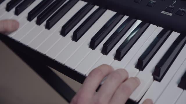 vidéos et rushes de jeune homme jouant la chanson romantique au piano, appréciant le passe-temps de musique, répétition - synthétiseur