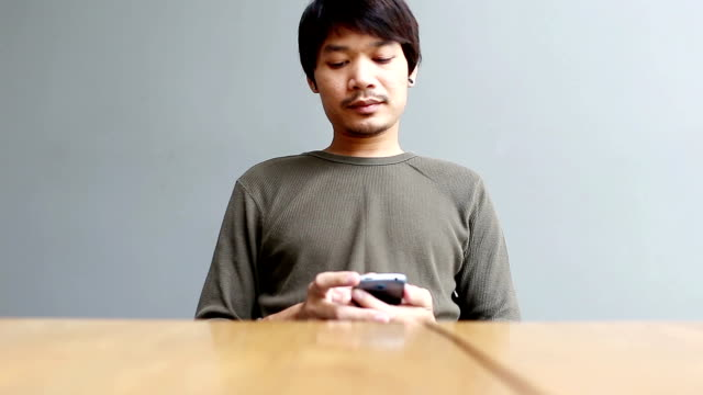Young man playing smartphone at home video