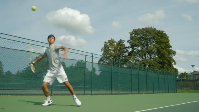 stockvideo's en b-roll-footage met een jonge man die tennissen speelt een geweldige schot van de basislijn en viert. - tennis