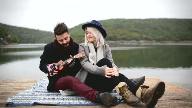 Young man playing ukulele to his girlfriend video