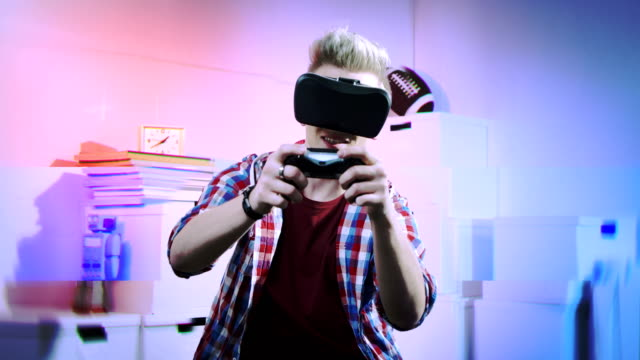 Young man playing with game controller using virtual reality video