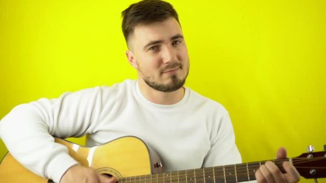 en ung man spelar gitarr och tittar på kameran. stilig vit man i vit tröja spelar gitarr. gul vanlig bakgrund - akustisk gitarr bildbanksvideor och videomaterial från bakom kulisserna