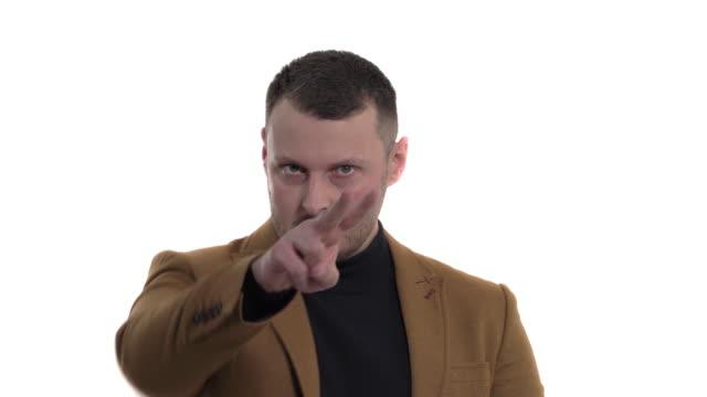 stockvideo's en b-roll-footage met jonge mens die naar iemand in de afstand richt en dreigend gebaar toont. geïsoleerd, over witte achtergrond - men blazer