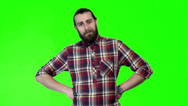 Young man posing on chromakey background Young satisfied bearded man in plaid shirt posing and gesturing on green chromakey background. arms akimbo stock videos & royalty-free footage