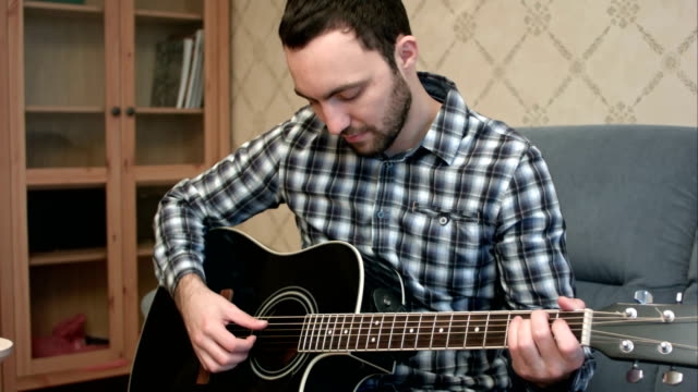 Young man practicing in playing guitar video
