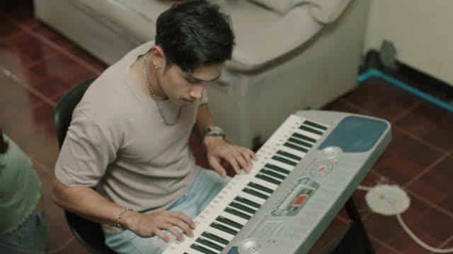 vidéos et rushes de jeune homme pratiquant le piano à la vidéo de stock à la maison - synthétiseur