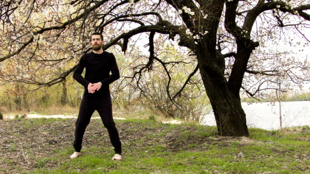 Young man practicing wing chun near the river