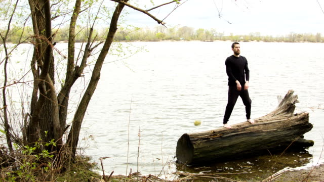 若い男が練習して川の近くの春を翼します。 ビデオ