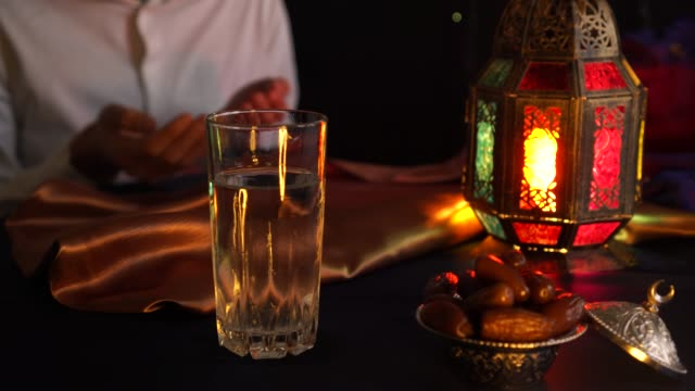 a young man prays and drinks water and eats dates. evening meal during the holy muslim month of ramadan - рамадан стоковые видео и кадры b-roll
