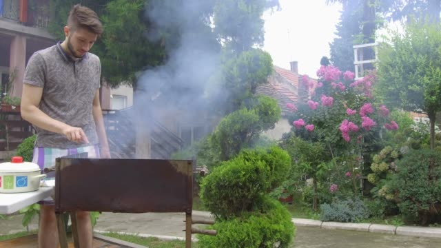 young man preparing barbecue - alla griglia video stock e b–roll