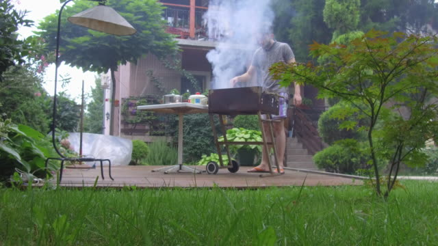 Young man preparing barbecue Young man preparing barbecue in formal garden formal garden stock videos & royalty-free footage